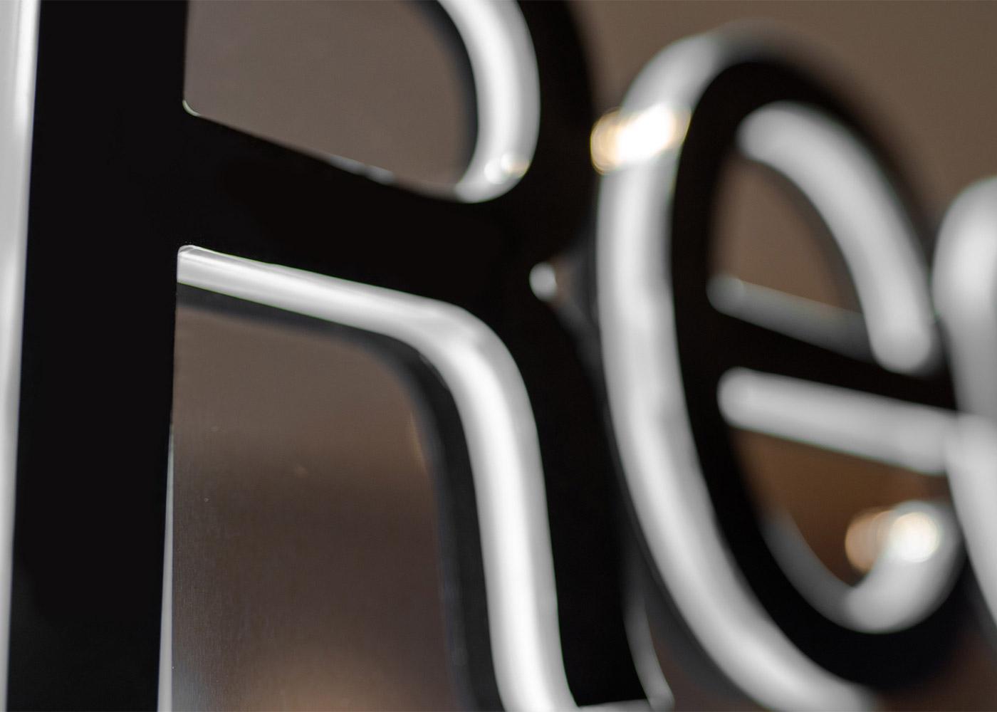 Closeup Regis Backlit Chrome Logo